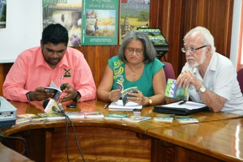 Minister of Tourism (ag) Irfaan Ali, publisher and editor of the 'Guyana where and what', Gem Madhoo-Nascimento and her husband Kit Nascimento browsing through the book