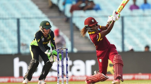 West Indies's Hayley Matthews(R)is watched by Australia's Alyssa Healy as she plays a shot during the World T20 cricket tournament women's final match between Australia and West Indies at The Eden Gardens Cricket Stadium in Kolkata on April 3, 2016. / AFP / DIBYANGSHU SARKAR (Photo credit should read DIBYANGSHU SARKAR/AFP/Getty Images)