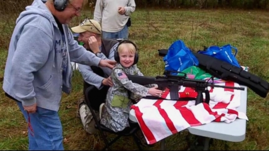 Four-year-old American child learns to us a machine gun